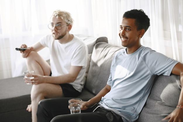 Homens indianos e europeus assistindo a filmes. eles estão sentados em um sofá.