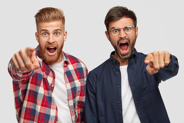 Homens irritados e raivosos com pelos grossos indicam com os dedos indicadores