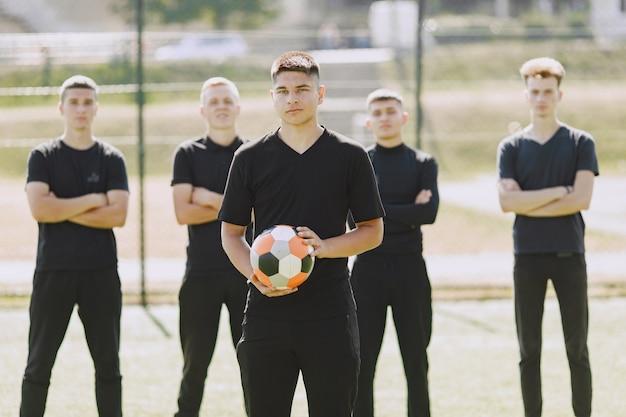 Homens jogam futebol no parque. torneio de mini futebol. cara em um traje esporte preto.