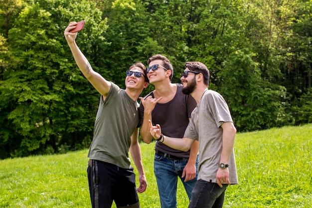 Homens jovens alegres, tendo selfie na natureza