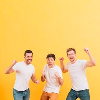 Homens jovens animados, cerrando o punho em pé contra um fundo amarelo