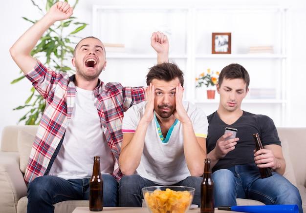 Homens jovens animados estão assistindo futebol em casa.