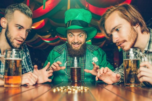 Homens jovens animados sentam-se juntos em uma mesa no pub. eles olham para moedas de ouro. caras têm canecas de cerveja na mesa. o homem no meio veste o terno verde de st patrick.