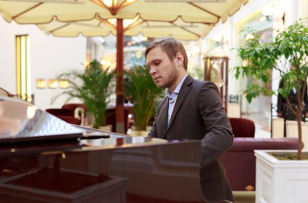 Homens jovens bonitos tocando piano