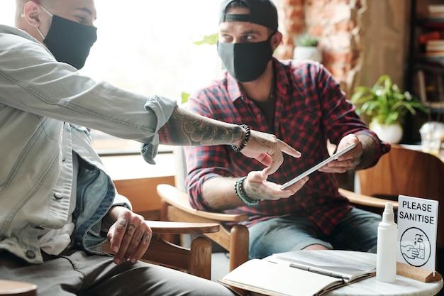 Homens jovens com máscaras de pano sentados no saguão e discutindo um novo aplicativo no tablet