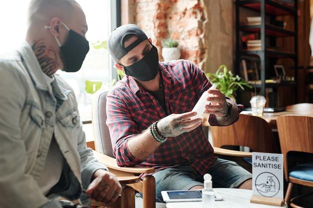 Homens jovens com máscaras pretas sentados em um café aconchegante e verificando o desinfetante enquanto lêem o rótulo.