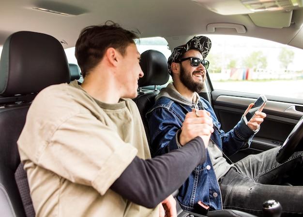 Homens jovens cumprimentando uns aos outros no carro