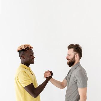 Homens jovens de cópia-espaço, apertando as mãos