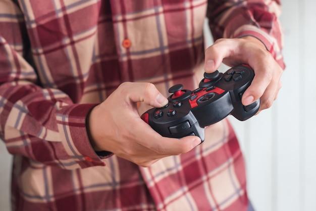 Homens jovens, desgaste, vermelho, scott, padrão, camisa, mão segurando, joystick, gamepad, jogo jogando