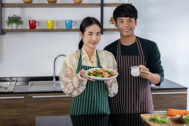 Homens jovens e meninas asiáticas estão mostrando salada de camarão