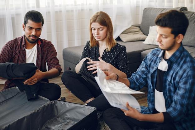 Homens jovens e mulheres se preparando para uma viagem. viajantes embalando roupas e bagagens em uma mala.