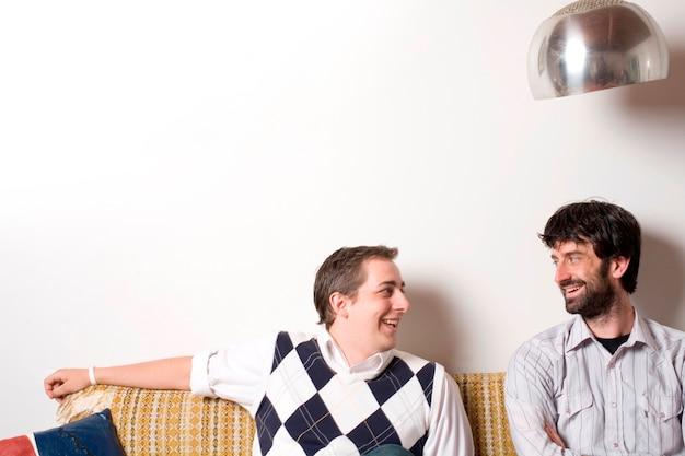 Homens jovens sentados no sofá falando