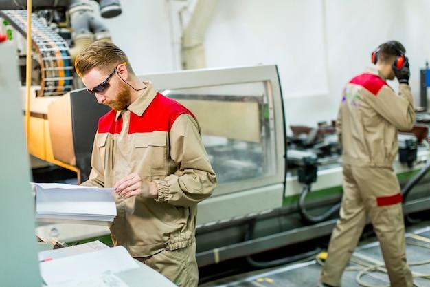 Homens jovens, trabalhando, em, mobília, fábrica