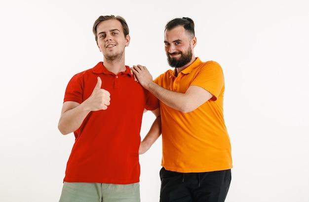 Homens jovens vestidos com as cores da bandeira lgbt, isoladas na parede branca. modelos masculinos caucasianos com camisas brilhantes. pareça feliz, sorrindo e se abraçando. orgulho lgbt, direitos humanos e conceito de escolha.