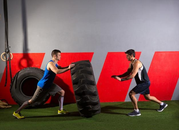 Homens lançando um exercício de ginásio de treino de pneu de trator