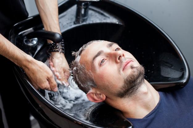 Homens lavam os cabelos em uma barbearia