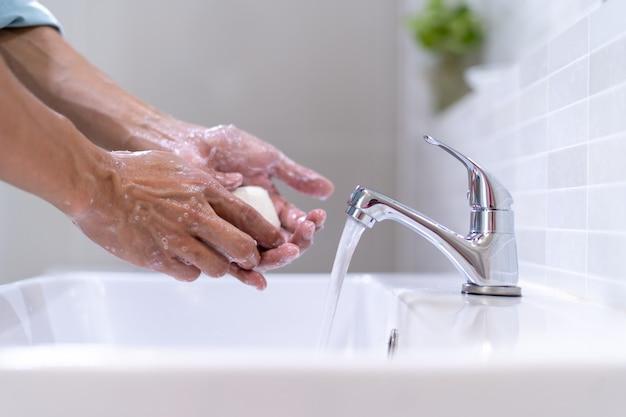 Homens lavando as mãos com sabão e água limpa em frente à pia do banheiro para evitar a propagação de germes. lavar as mãos com sabão.