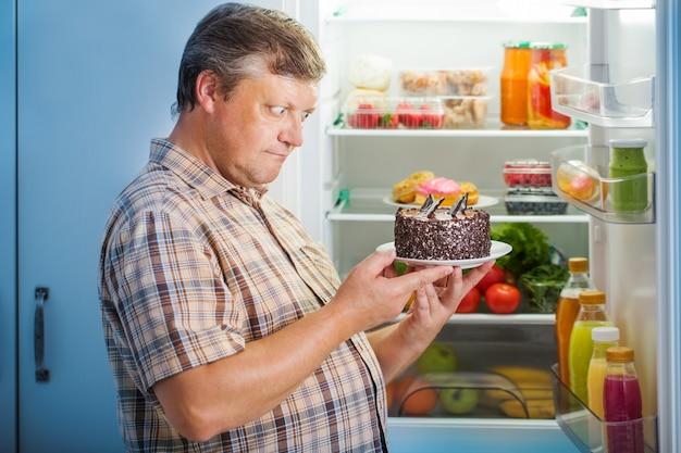 Homens maduros na geladeira com comida