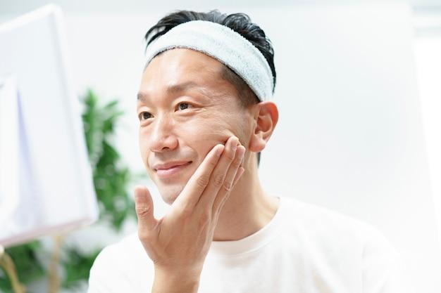 Homens médios asiáticos cuidando da pele na sala