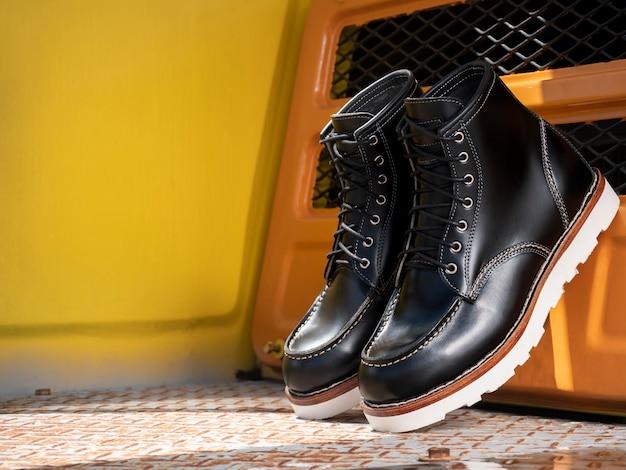 Homens moda botas pretas de couro no chão sobre amarelo.