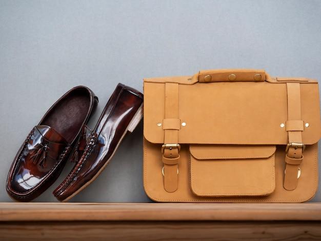 Homens moda conceito de roupas de verão com sapatos marrons e bolsa de couro na mesa de madeira