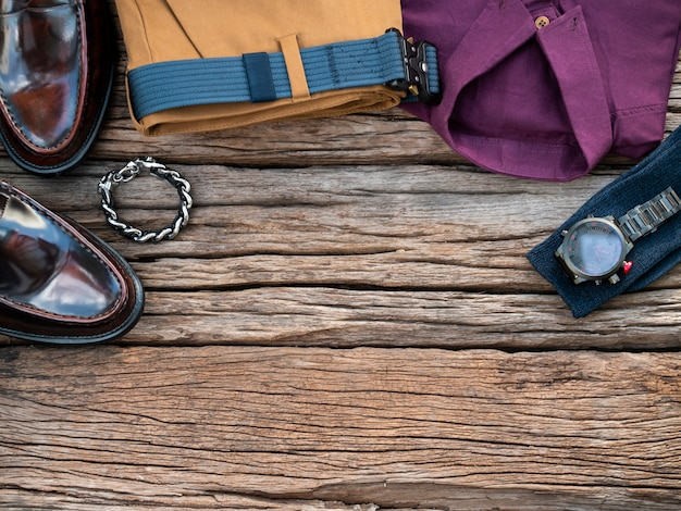Homens moda conjunto de roupas e acessórios em fundo de madeira.