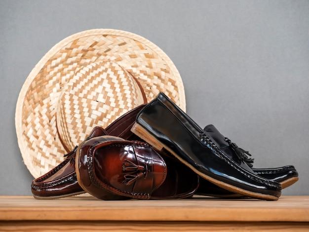 Homens moda sapatos borla mocassim e chapéu na mesa de madeira em cinza