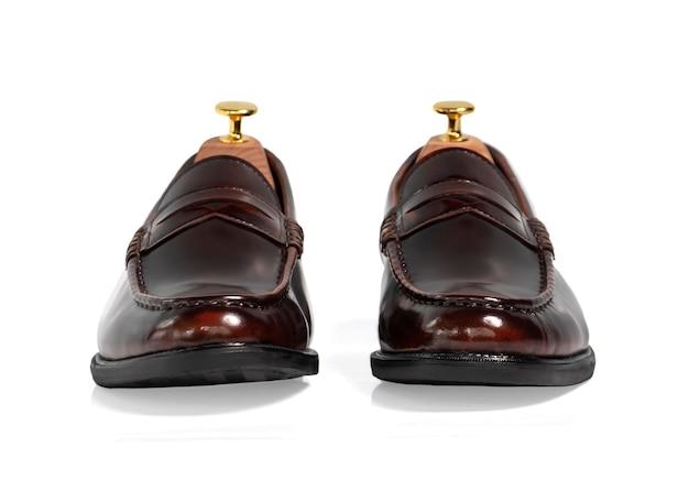 Homens moda sapatos de mocassim de coleção de couro polido marrom com árvore de sapato (suporte de forma) isolado no branco. vista frontal