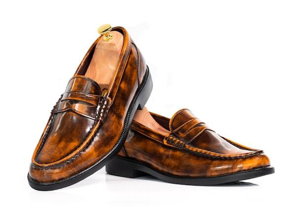 Homens moda sapatos de mocassim de coleção de couro polido marrom com árvore de sapato (suporte de forma) isolado no branco.