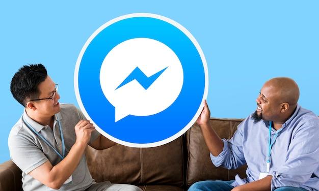 Homens mostrando um ícone do facebook messenger