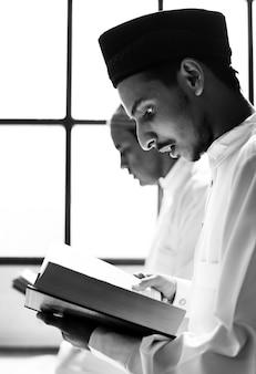 Homens muçulmanos lendo o alcorão durante o ramadã