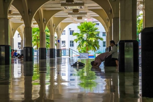 Homens muçulmanos orando e prostrados