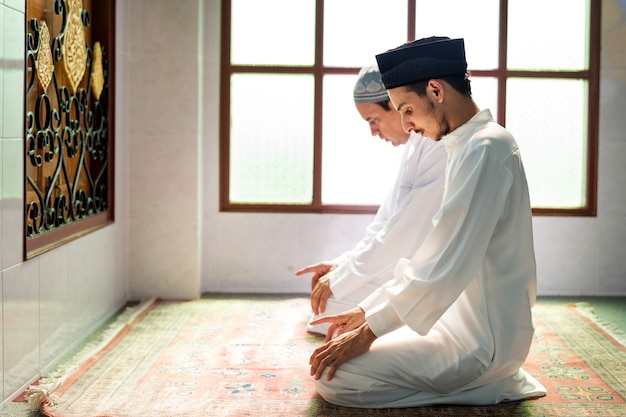 Homens muçulmanos rezando na postura de tashahhud