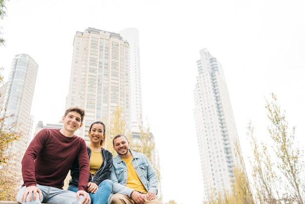 Homens multirraciais sorridentes e mulher sentados juntos no parque da cidade outono