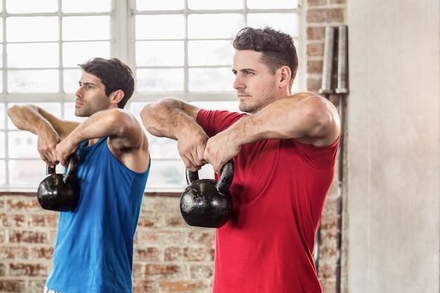 Homens musculares levantando um sino de chaleira