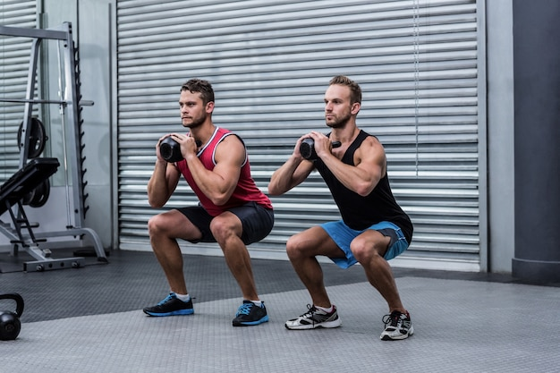 Homens musculosos exercitando com kettlebells
