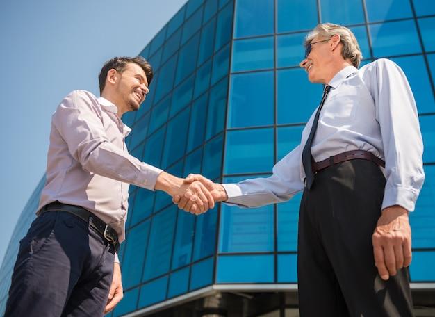 Homens negócio, apertar mão, enquanto, ficar, frente, escritório