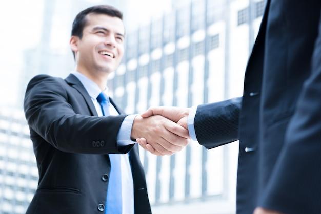 Homens negócios, fazer, aperto mão, frente, edifícios escritório, cidade