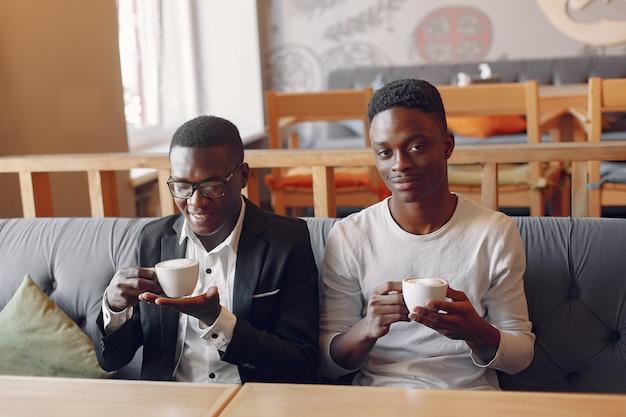 Homens negros, sentado em um café e bebendo um café