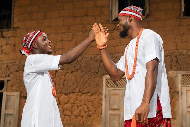 Homens nigerianos com tiro médio do lado de fora
