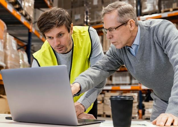 Homens no armazém trabalhando em um laptop