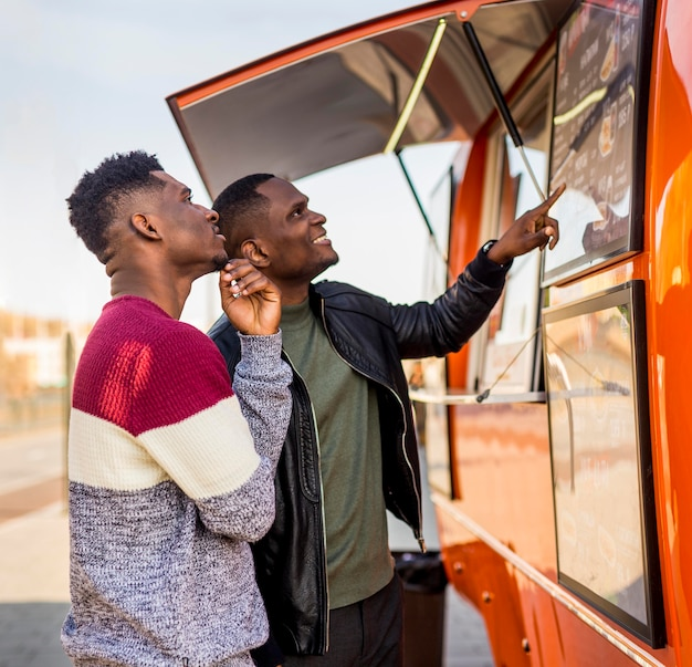 Homens no meio do tiro lendo cardápio de food truck
