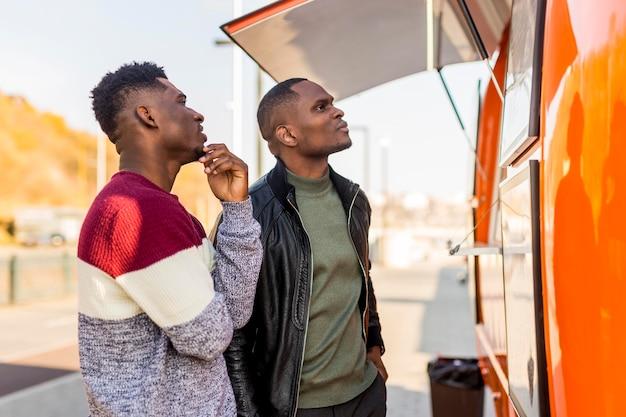Homens no meio do tiro lendo o menu do food truck