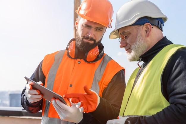 Homens olhando para um tablet, tiro médio