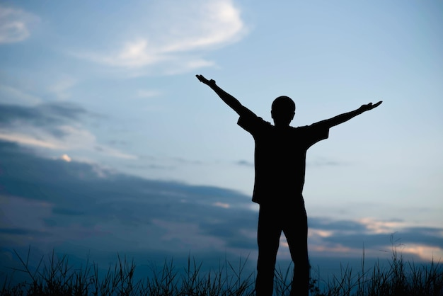Homens, que acolhem o nascer do sol com as mãos levantadas e apreciando a paisagem.