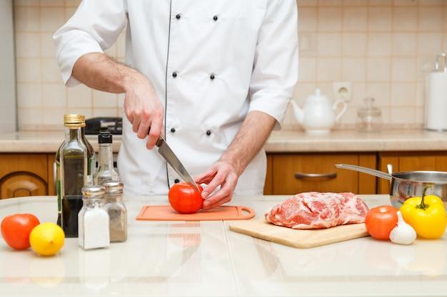 Homens que cortam o tomate na placa de corte com faca afiada.