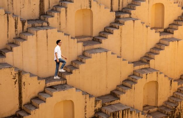 Homens que cruzam os poços em degraus de chand baori em jaipur na índia.
