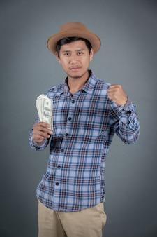 Homens que guardam um banco do dólar em um fundo cinzento.