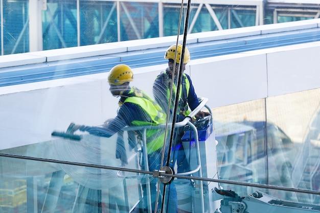 Homens que limpam janelas. dois trabalhadores lavando janelas do edifício empresarial moderno.