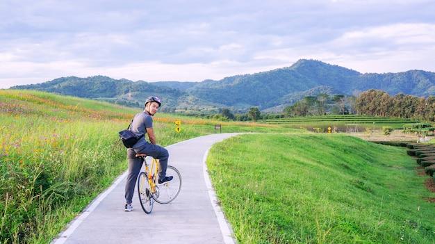 Homens que montam uma bicicleta perto de um lago no parque chiang rai de singha, tailândia.
